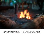 knife in wood by fire - stock photo