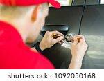 locksmith opening car door with ... | Shutterstock . vector #1092050168