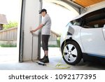 a man charging electric car  at ... | Shutterstock . vector #1092177395