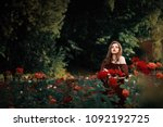 Stock photo beautiful young woman in red dress with long curly hair posing near roses in a garden the concept 1092192725
