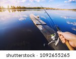 hand with spinning and reel on... | Shutterstock . vector #1092655265