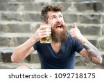 Small photo of Happy bearded man having a drink after long day in office. Cheerful tipsy man holding beer mug while showing thumb up gesture, relax after work and weekend concept