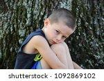 little boy sits besides a tree...   Shutterstock . vector #1092869102