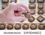 Small photo of Focus on goody set in golden carton. Different shapes and tastes candies packed into special design case. Arm and chocolate sweetmeat with round form and curved lines.