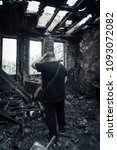 Small photo of Sad man in burnt house. Loss and despair concept.