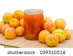Heap apricots and a glass jar with apricot jam - stock photo