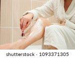 beautiful girl shaving her legs ... | Shutterstock . vector #1093371305
