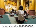 Burmese Women Sit Chanting To...