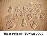 Lots Of Hand Prints On The Sand.