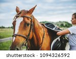 a woman jockey removes the... | Shutterstock . vector #1094326592