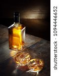 Small photo of view of glass of whiskey and a bottle aside on color background.
