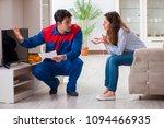 repairman repairing tv at home | Shutterstock . vector #1094466935