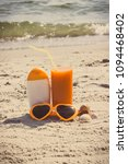 Small photo of Vintage photo, Carrot juice, sunglasses and sun lotion, concept of prevention of vitamin A deficiency, beautiful and lasting tan