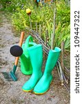 Green garden watering-can, rubber knee-boots and rakes - stock photo