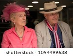 Small photo of Windsor, Berkshire, England - May 19 2018 : Portrait of a elderly American couple sitting in the shade of a shop window ahead of the Royal Wedding of Prince Harry and Meghan Markle