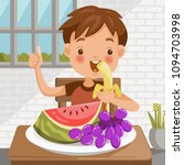 boy eating fruit. sitting at... | Shutterstock .eps vector #1094703998