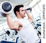 Handsome Gym Man Lifting Heavy...