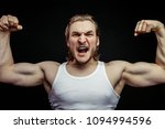 Small photo of angry jock showing his musculars isolated on the black background. rage concept. violent sport