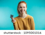 Small photo of Attractive ginger adult woman holding condom calling to prevent sexually transmitted diseases or unwanted pregnancy