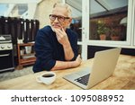 smiling senior man sitting at a ... | Shutterstock . vector #1095088952