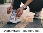 female jogger tying shoes...   Shutterstock . vector #1095092408