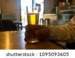 glass of fresh beer in hand | Shutterstock . vector #1095093605