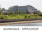 View on campus building of Far Eastern Federal University (former Far Eastern State University). Many people walk by embankment in a sunny day. Russia, Vladivostok.