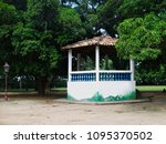 small white bandstand with blue concrete grids in the middle of large trees, Taubate, SP, Brazil