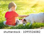 cute baby boy sitting in grass... | Shutterstock . vector #1095526082