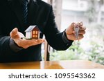 hands holding small house after ... | Shutterstock . vector #1095543362