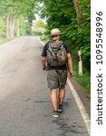 man with backpacks walks alone... | Shutterstock . vector #1095548996