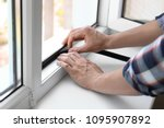 young man putting sealing foam... | Shutterstock . vector #1095907892