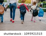 Stock photo mother and pupil and kids holding hands going to school in first class with schoolbag or satchel 1095921515