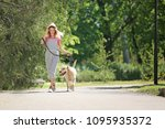 Stock photo young woman and her dog spending time together outdoors pet care 1095935372