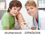 Putting a bandaid on wound - boy in emergency room - stock photo