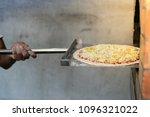 man putting pizza baking sheet... | Shutterstock . vector #1096321022