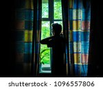 Small photo of alone man silhouette staring at the window closed with curtains in bedroom