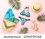 Bikini swimsuit with tropical print, silver glitter flat sandans, straw hat, wicker beach bag, sarong, tropical palm leaves on pink background. Overhead view of woman