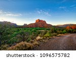 Tahe me home county road - a beautiful Sedona Arizona landscape.  With a road in the foreground, red rock formations and clouds and blue skies, this image invites the viewer to take a trip. - stock photo