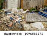 Small photo of Large pile of rubbish, rotting after being fly tipped and left in an urban alleyway. Demonstrates anti-social behaviour.