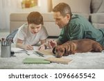 Stock photo focus on dachshund puppy getting bored while her owners are involved in doing homework pet is 1096665542