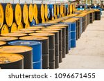 Small photo of Industry oil barrels or chemical drums stacked up.container of barrels of hydrocarbons.hazardous waste of black and blue tank oil.Stack Of Oil barrels in plant.