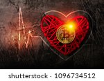 Small photo of Coin Bitcoin lies on a red heart, against a dark background. Palpitation