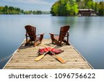 two muskoka chairs sitting on a ... | Shutterstock . vector #1096756622