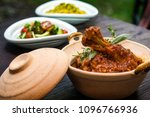 Spicy Reddish Chicken Curry / Masala, with prominent Leg Piece, served in a bowl or Kadhai over colourful or wooden background. selective focus.