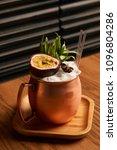Small photo of Spicy Mule cocktail on bar table. Alcoholic beverage drink with Rum angostura, reserve rum, dry orange passionfruit ,pure, pineapple pure, spice syrup ingredients, close-up