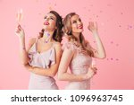 Stock photo photo of two young party women smiling and drinking champagne from glasses while standing under 1096963745
