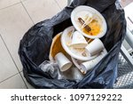 Small photo of Environment unfriendly styrofoam plates and cups disposed in plastic garbage bag