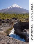Small photo of Vertical view with Osorno volcano on the background, with one of Pretohue falls on the foreground, on a clear sunny day in the summer or spring, in Vicente Perez Rosales National Park, Chile