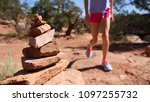 a girl hikes nearby a cairn on... | Shutterstock . vector #1097255732